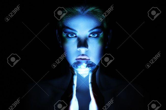 14175885-Hermosa-mujer-con-joya-grande-en-la-oscuridad-Foto-de-archivo