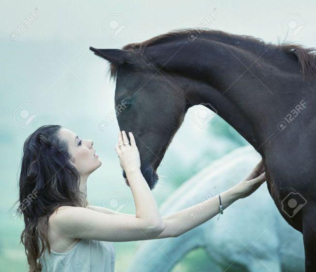 20784848-mujer-sensual-acariciando-un-caballo-salvaje-foto-de-archivo